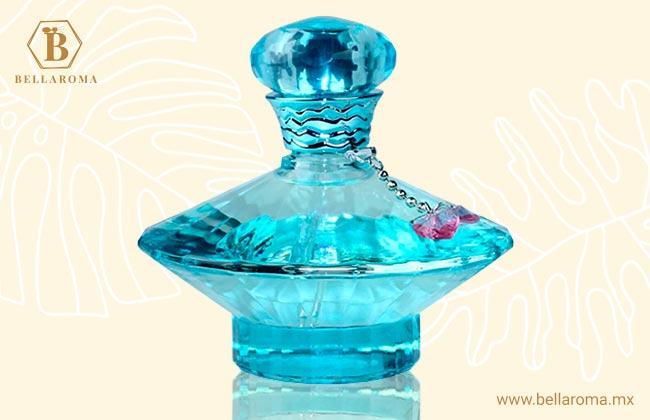 frasco de perfume fresco britney spears curious en fondo tropical